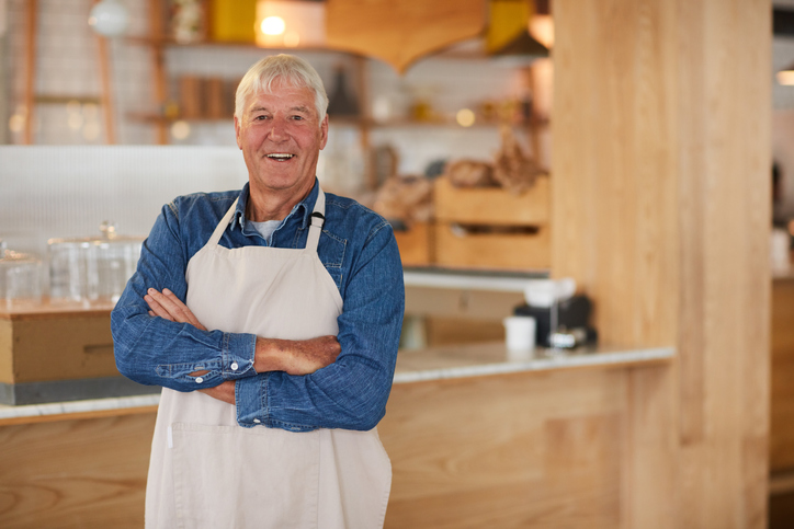 Portrait of a confident senior business owner posing with an apron on in his coffee shop